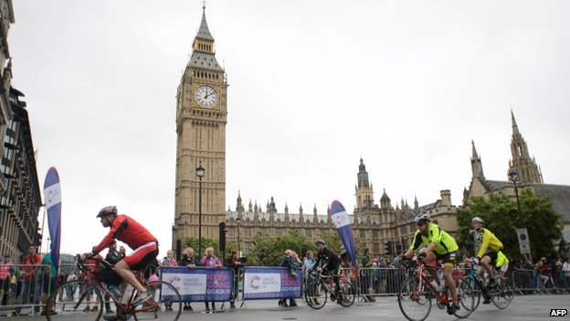 Cyclists ride past the Houses of Parliament in central London