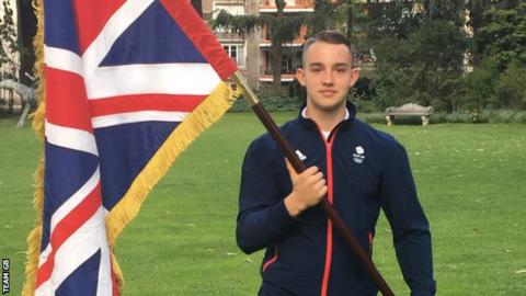 BMX rider Ross Cullen holds up the Union Jack after being selected as Team GB's flag-bearer at the Youth Olympics opening ceremony
