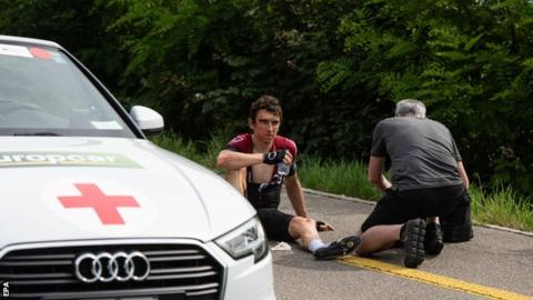 Geraint Thomas being treated by a medic after crashing