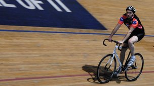Neil Heath riding a bicycle in a velodrome