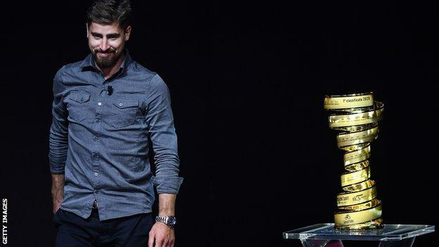Cyclist Peter Sagan stands next to the Giro d'Italia trophy at the route presentation