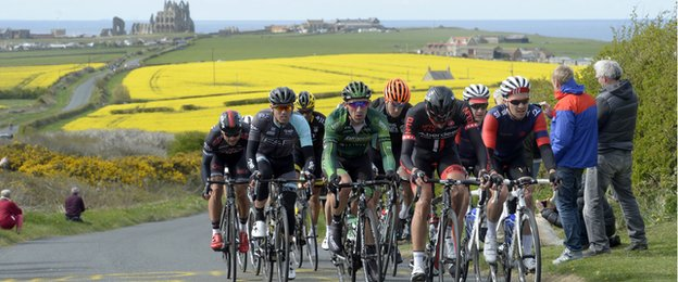 The peleton in the Tour de Yorkshire passes Whitby Abbey