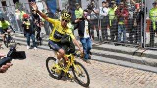 Colombia's Tour de France winner Egan Bernal waves as he rides his bike upon his arrival in his hometown Zipaquira, Cundinamarca, Colombia