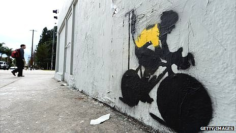 Los Angeles graffiti depicting a cyclist   in a yellow jersey, the traditional garb of a Tour de France winner, attached to an IV drip. Lance Armstrong was stripped of 7 TDF titles